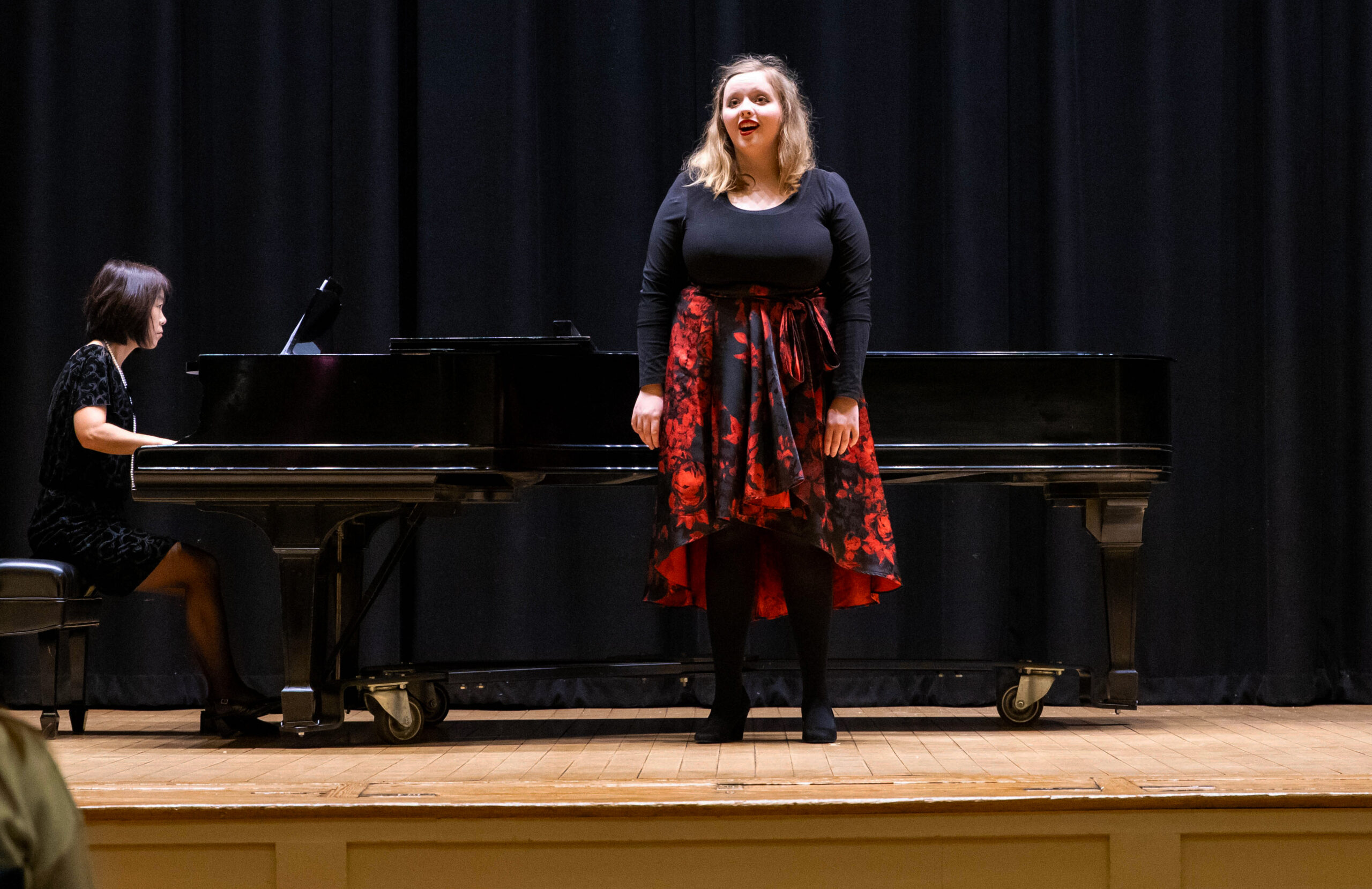 Young white female student singing with a pianist